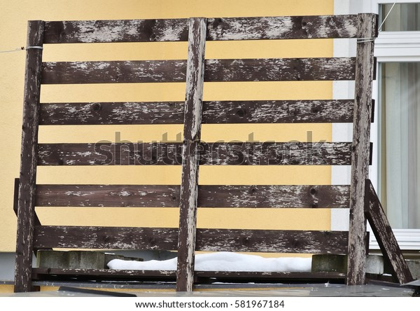 Wooden pallet on a tin roof before the window  /  Wooden pallet