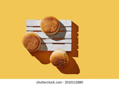 Wooden pallets with buns on yellow pastel background