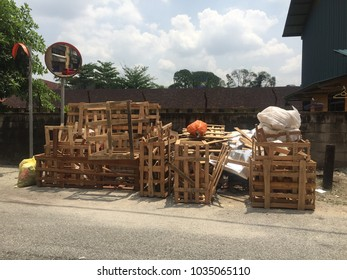 Wooden pallets dumped behind the building and in the trash at the edge of a junction