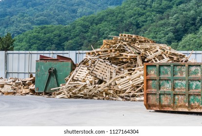 Wooden pallets stacked haphazardly next to green metal trash receptacles in  industrial park in mountain.