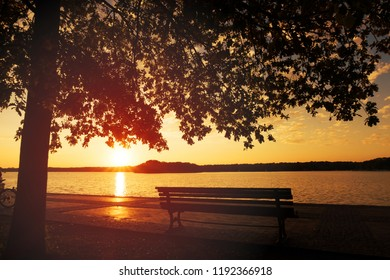 Wooden Park Bench at the Lakeshore at Sunset