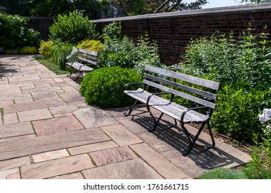 Wooden park benches in a garden in Mellon Park on a sunny summer day, Pittsburgh, Pennsylvania, USA