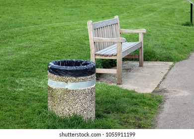 Wooden park seat on a concrete plinth with an adjacent concrete litter bin containing a black plastic bin liner with grass lawn in the background.