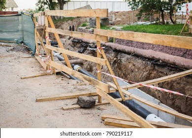 Wooden partition for security. Water pipes with insulation lie on the ground. Construction works.