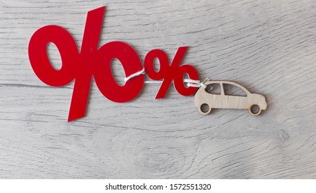 Wooden passenger car model and percent sign on a wood background. The concept of change of car prices .