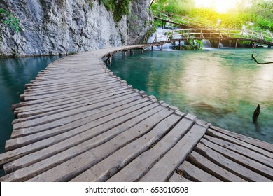 Wooden path across beautiful lake and waterfall in sunny green forest