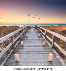 Wooden path at Baltic sea over sand dunes with ocean view, romantic sunset summer evening