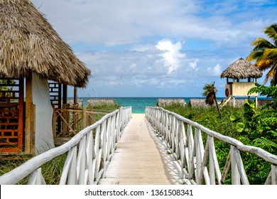 Wooden path at Caribbean sea over sand dunes with ocean view, day time. Wooden walkway leading to a beautiful tropical beach in Cuba