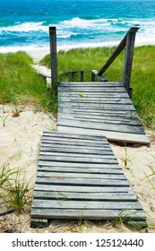 Wooden path down to the beach and ocean.  Walkway and stairs through sand dunes and grass.