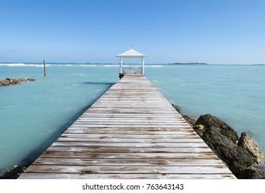 The wooden path leading to gazebo on Nassau city Sandyport beach (Bahamas).