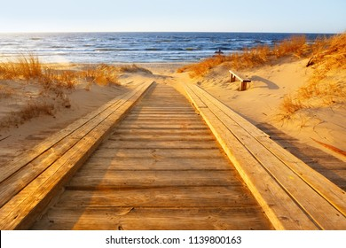 Wooden path to the sea. Sunny autumn day on the Baltic sea. Sandy beach, dunes and yellow grass