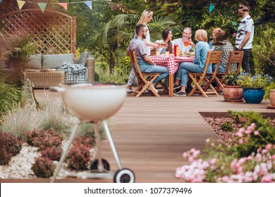 Wooden patio in the garden with a grill standing in the front and happy young people gathered around a table full of food during summer brake meeting