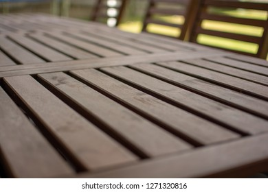 Wooden patio table. Consisting of timber stained slate with chairs blurred in the background.
