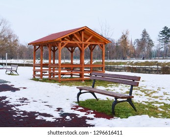 Wooden pavilion and empty benches in the snow covered landscape.