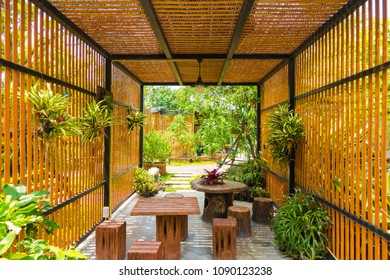 Wooden pavilion home with Patio furniture in garden.