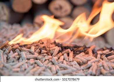 Wooden pellets in flames - wooden biomass, renewable energy