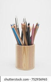 Wooden pencil holder with crayons and brushes