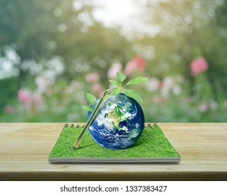 Wooden pencil, tree trunk and leaves with planet earth on an open book on table over blur pink flower and tree in garden, Idea for earth concept, Elements of this image furnished by NASA