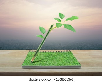 Wooden pencil with trunk tree and leaves on an open book on wooden table over office city tower at sunset, vintage style, Green ecology idea concept
