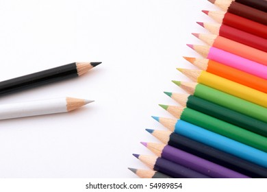 Wooden pencils of different colour on a white paper.