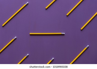 Wooden pencils with eraser tops arranged parallelly and only  one in horizontally, out of context, with space for text, on a purple background.