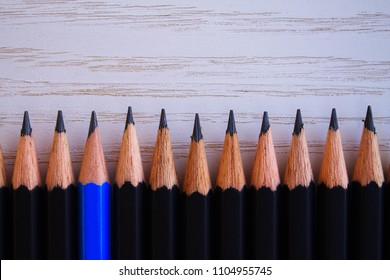 Wooden pencils with one different color, placed in row on surface of a table.