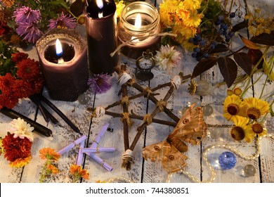 Wooden pentagram with moth - death symbol, black candles and flowers on planks. Occult, esoteric, divination and wicca concept. Halloween vintage background