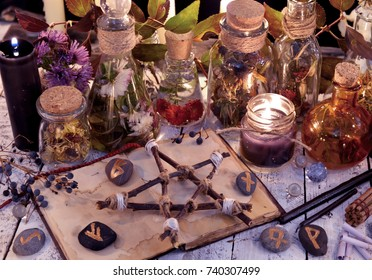 Wooden pentagram, open book, glass bottles, flowers, candles and runes on witch table. Occult, esoteric, divination and wicca concept. Alternative medicine vintage background