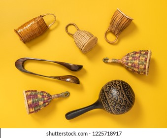 Wooden percussion musical instruments on yellow background. Caxixi shakers, maracas and musical spoons.