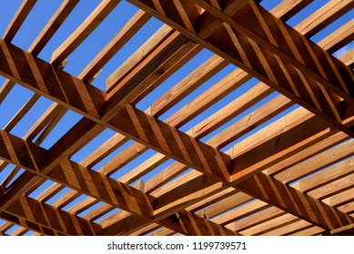 wooden pergola in the sun with blue sky