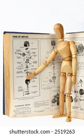 A wooden person teaching about a car repair from a technical manual