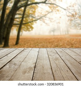 Wooden perspective floor with planks on blurred natural autumn background, can use for display or montage your products template. Copy space