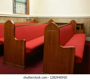 Wooden pews with red cushions; crosses carved on the sides.  Pews located in front, left corner of a church in Baltimore.  Burgundy carpet.  Wood paneling.  Cream-colored walls.  Stained glass window.