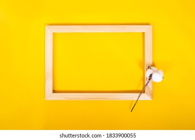 Wooden photo frame with cotton on yellow background. Layout, copy space