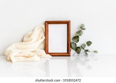 Marco fotográfico de madera con un sorbo de eucalipto sobre una mesa blanca de madera. Diseño minimalista y delicado. En blanco para una postal.