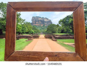 Wooden photoframe for composition with landscape of Sigiriya mountain and famous historical and archaeological site. Road through the forest around UNESCO world heritage site.
