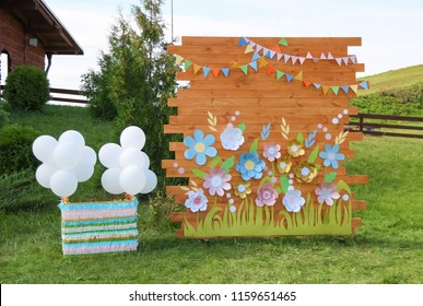 Wooden photozone for children's holiday. Photozone from a tree with paper flowers for a children's birthday.