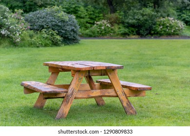 Wooden picnic table with benches on beautiful green grass lawn in quiet place
