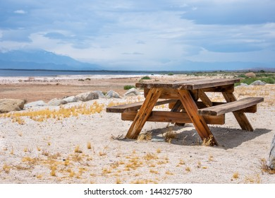Wooden picnic table on a white sand beach at a lake side;  California desert - Salton sea recreation area