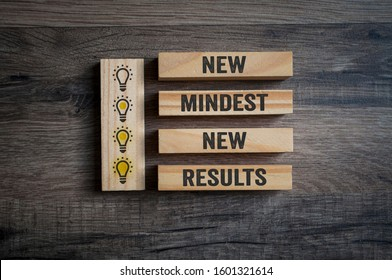 Wooden pieces on a wooden background showing the words new mindset and new results