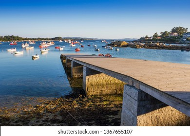 Wooden pier and anchored fishing boats on Campo harbor in Arousa Island