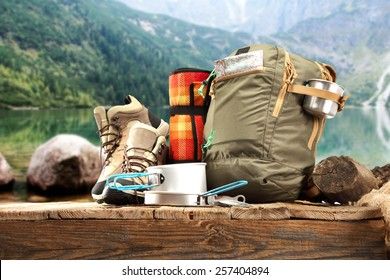 wooden pier and backpack and shoes of brown color and lake of green color at summer time