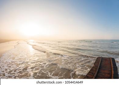 Wooden pier. Beach of Lido di Jesolo at adriatic Sea in a beautiful summer day Italy. near Venice. dense sea breeze at dawn
