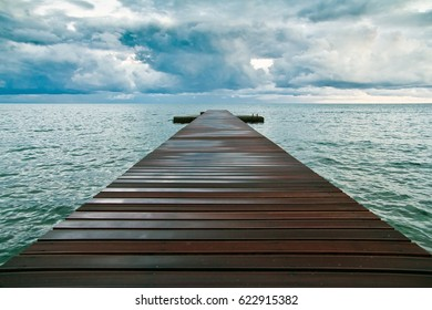 A wooden pier in blue sea and big clouds over it in Budva, Montenegro