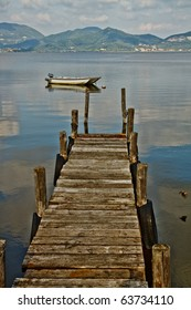 Wooden pier and boat on Lake. Tuscany, Italy