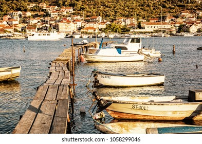 Wooden pier with boats in harbor, Trogir, Croatia. Travel destination. Sunset scene. Yellow photo filter.
