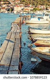 Wooden pier with boats in harbor, Trogir, Croatia. Travel destination. Sunset scene. Vertical composition. Retro photo filter.