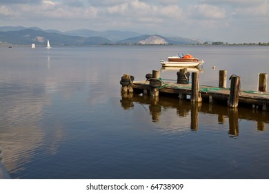 Wooden pier and boats on Lake in Tuscany, Italy