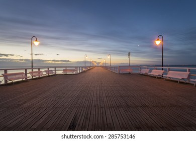 wooden pier by the sea lit by stylish lamps at night
