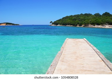 Wooden pier by the turquoise water, islands in the background in Ksamil, Sarande, Albania, paradise looking scene, no trash, no litter, clean beach. Albania is very beautiful and interesting country!